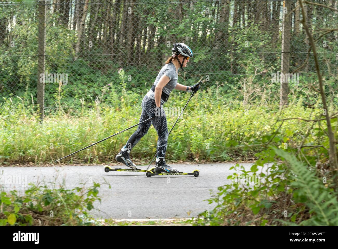 woman-roller-skiing-on-a-quiet-road-aldershot-uk-2CAWWET.jpg