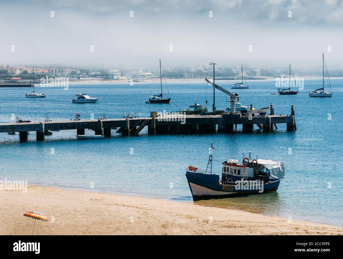 wooden-fishing-boat-moored-on-empty-ribeira-beach-in-cascais-portugal-with-scenic-background-2CC99FE.jpg