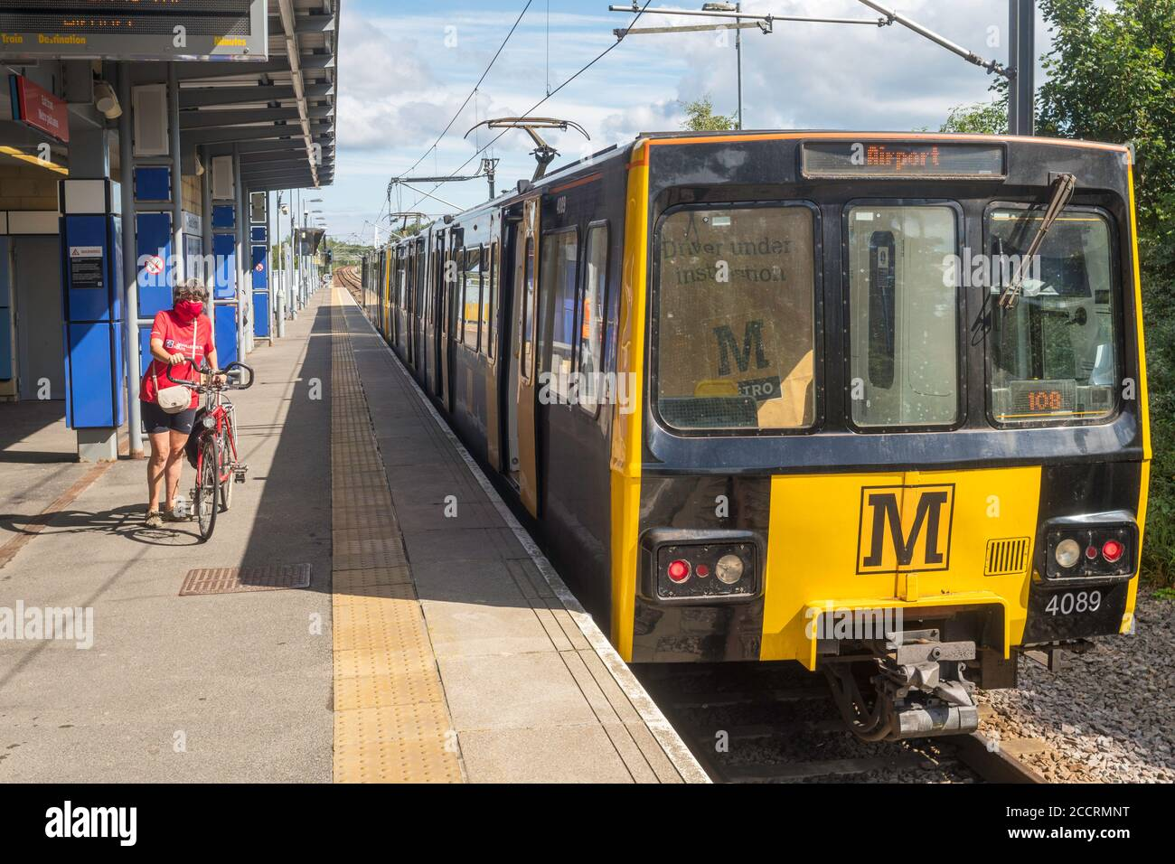 mature-female-cyclist-wearing-face-mask-with-bike-on-tyne-and-wear-metro-south-hylton-station-north-east-england-uk-2CCRMNT.jpg