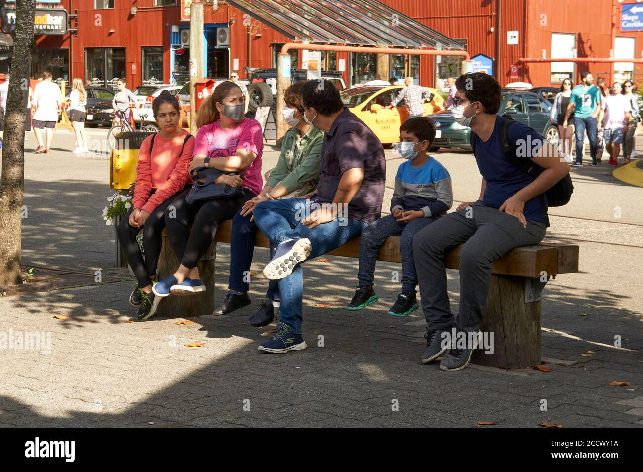 a-family-sitting-on-a-bench-wearing-prot