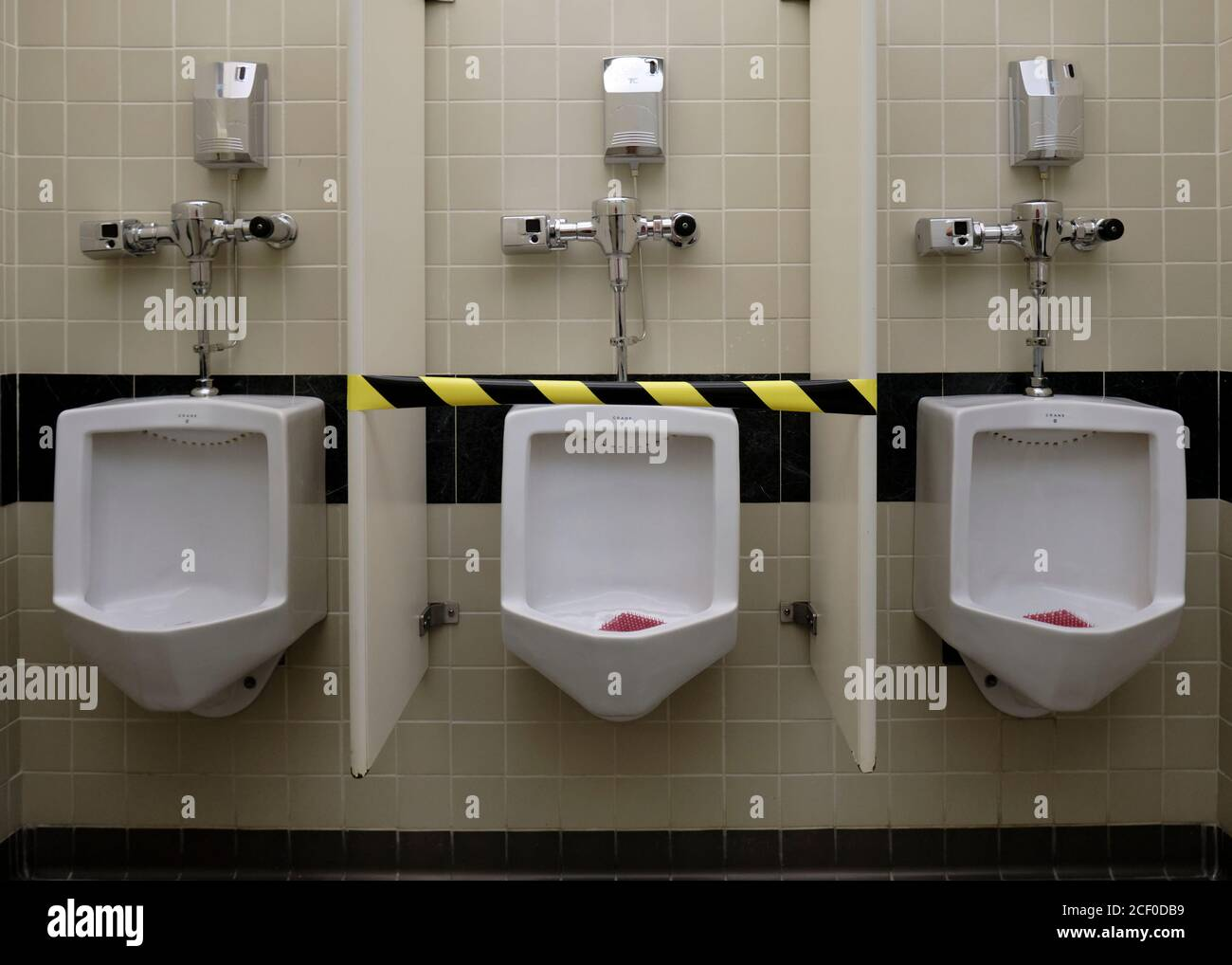 set-of-three-urinals-with-the-middle-one-taped-up-and-out-of-usage-based-on-covid-19-health-guidelines-2CF0DB9.jpg