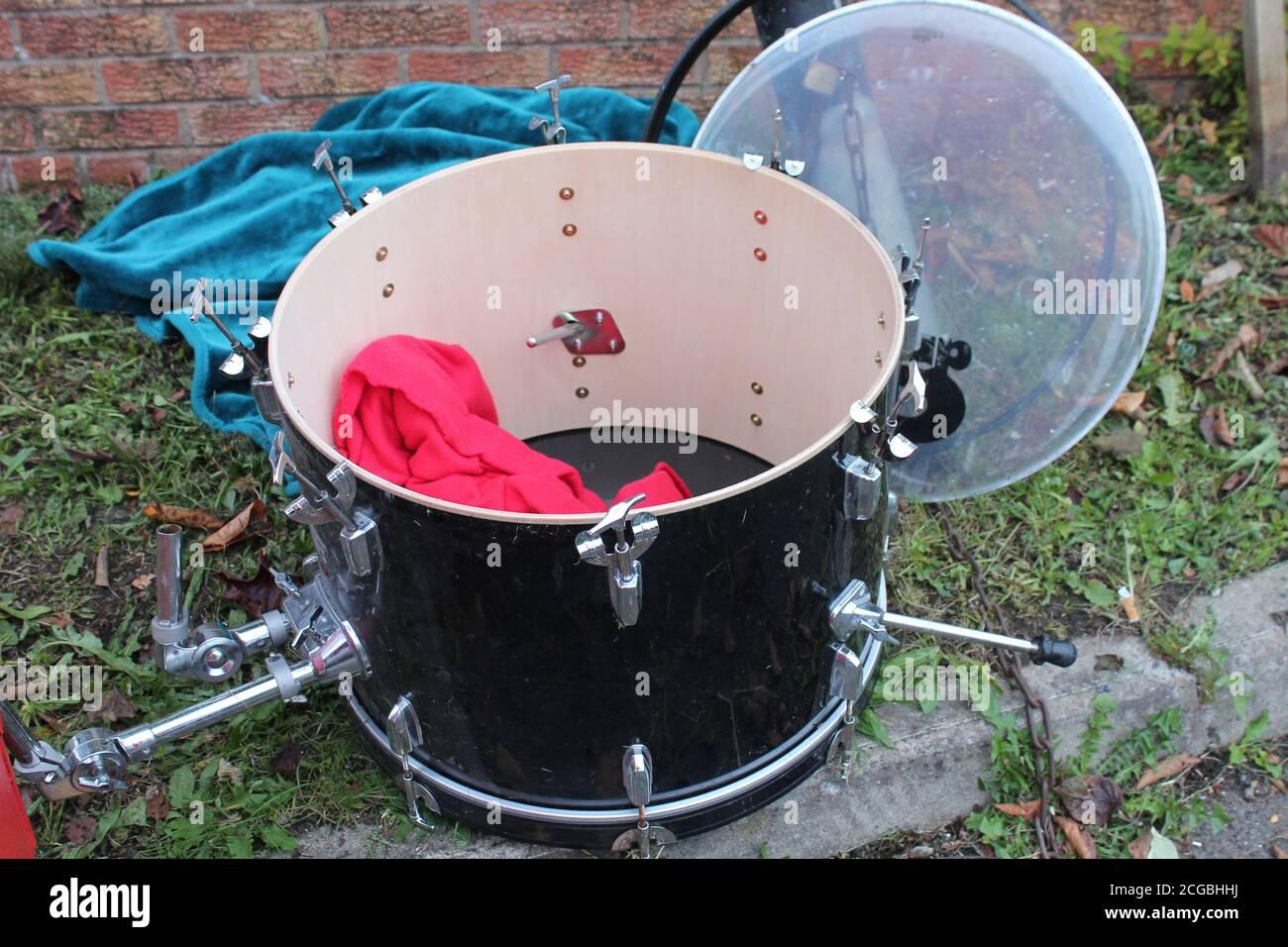 Broken drum discard on the grass verge Stock Photo