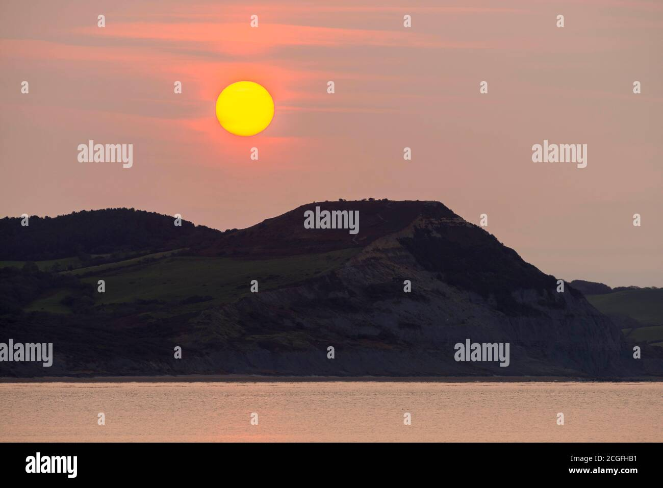 Lyme Regis, Dorset, UK.  11th September 2020.  UK Weather.  View from Lyme Regis in Dorset at sunrise as the sun rises up through the thin hazy cloud from behind Golden Cap on the Jurassic Coast.  Picture Credit: Graham Hunt/Alamy Live News Stock Photo