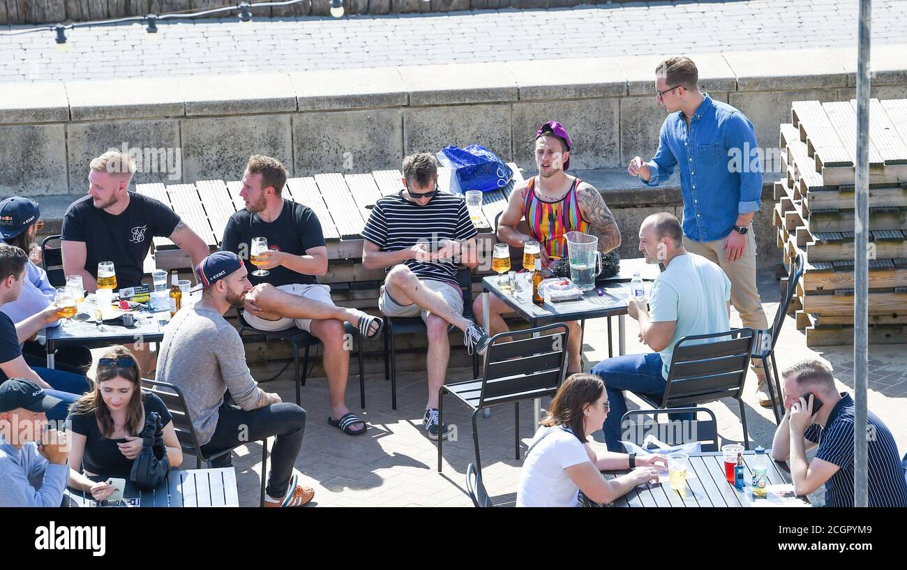 Brighton UK 12th September 2020 - Time to enjoy a beer on Brighton seafront on a sunny but breezy day as hot weather is forecast to spread across Britain over the next few days ..   : Credit Simon Dack / Alamy Live News Stock Photo