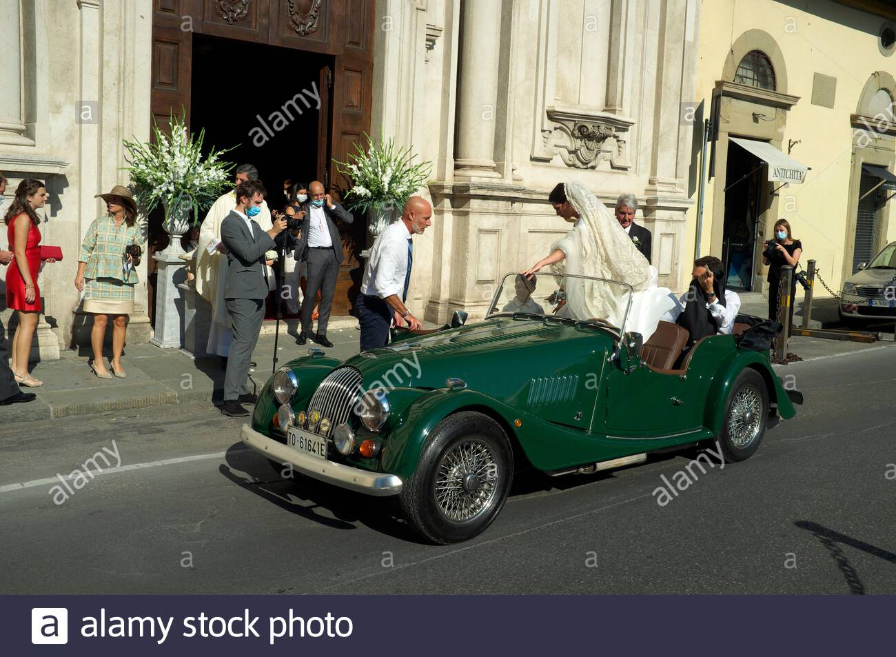 Bride & groom arrive at the church of San Salvatore di Ognissanti in a Morgan sports car. Florence, Tuscany, Italy. Stock Photo
