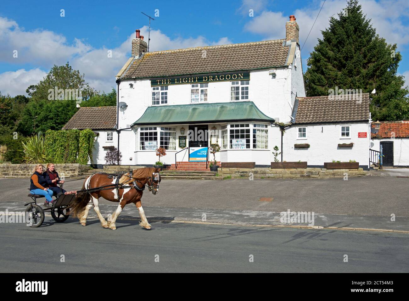 two-women-on-horse-and-trap-in-the-village-of-etton-east-yorkshire-england-uk-2CT54M3.jpg
