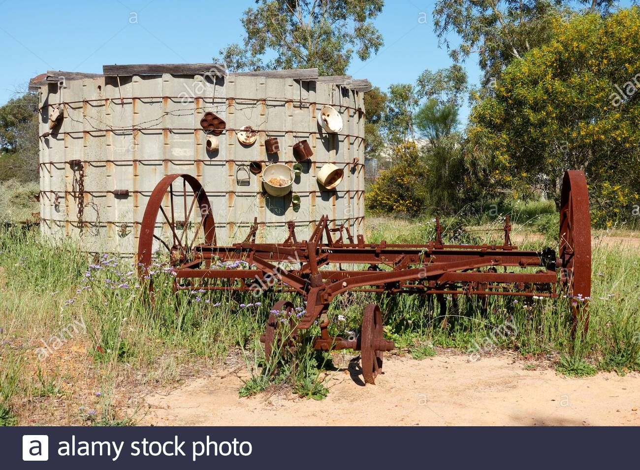 old-farm-machinery-and-rusted-pots-and-other-objects-attached-to-a-water-tank-at-the-base-of-mingenew-hill-in-the-town-of-mingenew-western-australia-2CTAC0Y.jpg