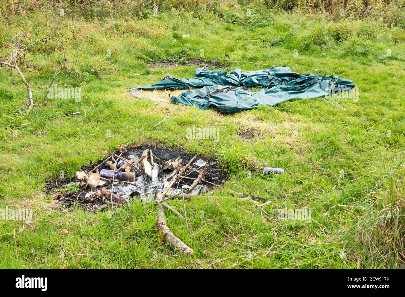 Abandoned tent and camp fire with discarded drinks cans and bottles, illegal camping, north east England, UK Stock Photo