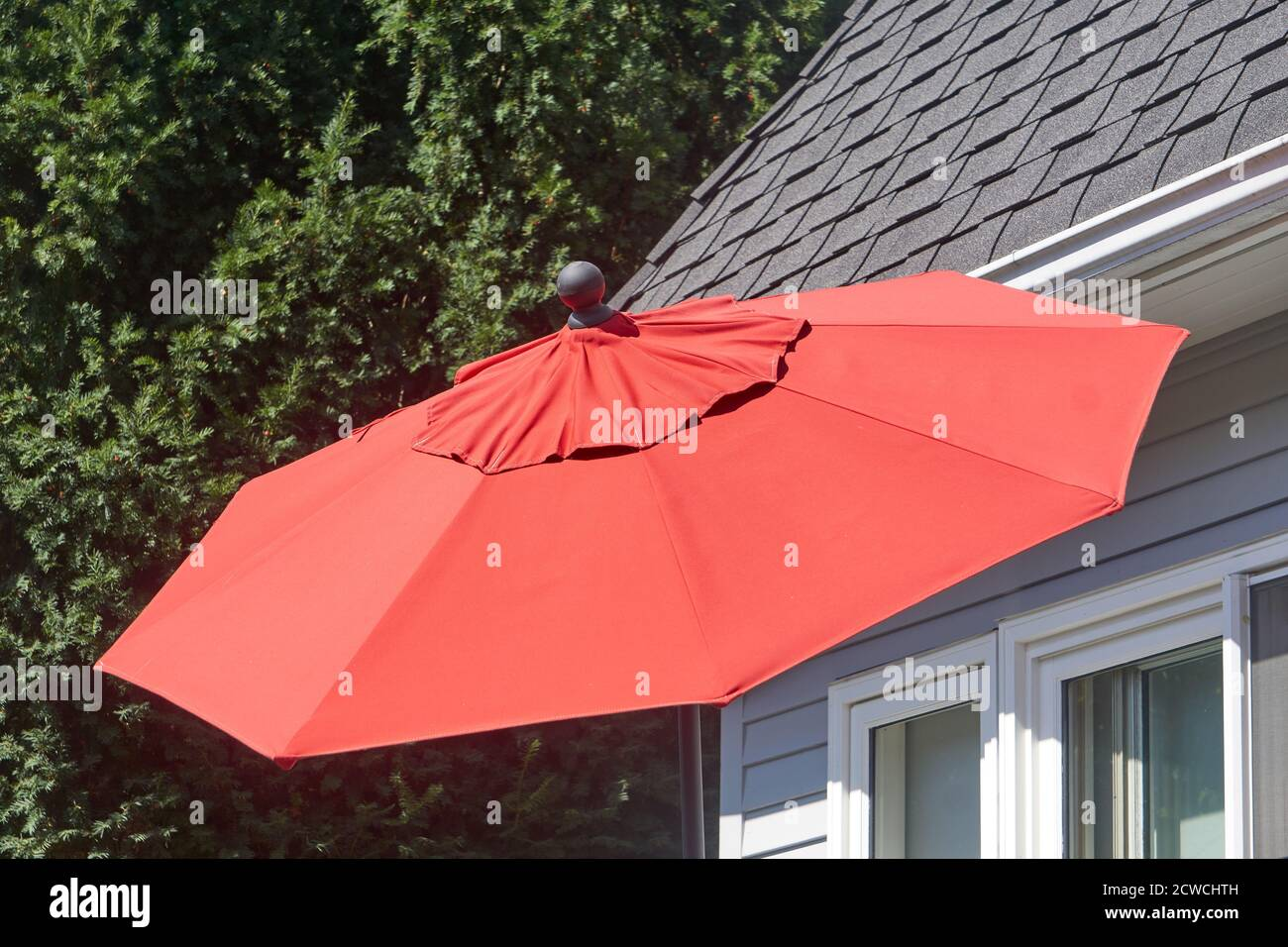 Big red outdoor umbrella outside a house Stock Photo