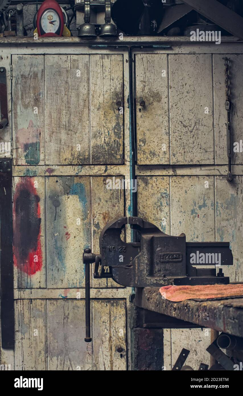 old-ancient-record-vice-in-front-of-a-white-distressed-dirty-paint-spattered-old-cupboard-in-a-cluttered-old-workshop-mudeford-uk-2D23ETM.jpg