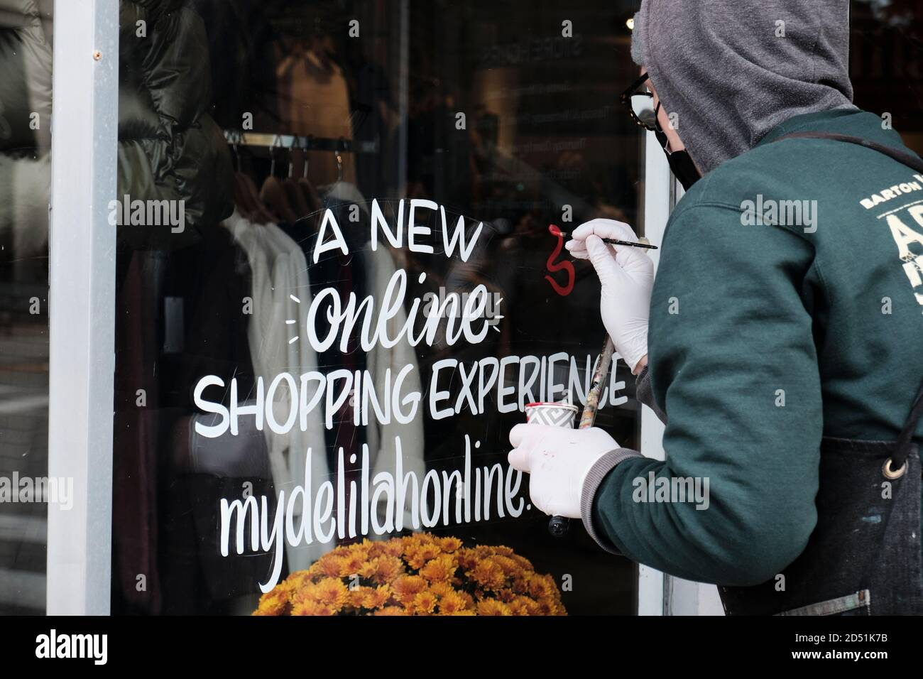 artist-painting-old-fashioned-hand-lettered-window-lettering-sign-on-store-due-to-impact-of-pandemic-the-local-artist-has-seen-increase-demand-2D51K7B.jpg