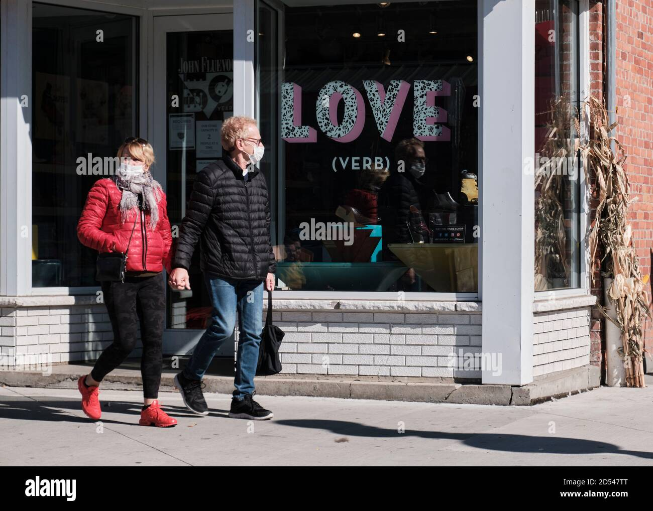 couple-walking-holding-hands-by-store-window-with-the-word-love-printed-they-are-not-looking-at-eachother-2D547TT.jpg