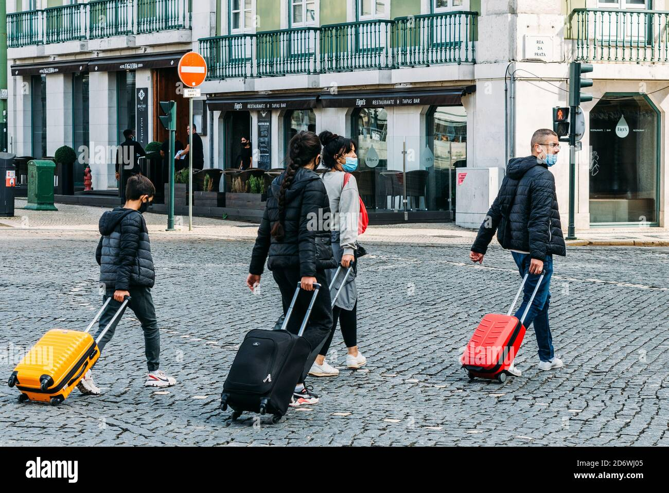 lisbon-portugal-october-18-2020-family-each-wearing-face-masks-carrying-luggage-in-the-historic-centre-of-lisbon-portugal-travel-during-covid-2D6WJ05.jpg