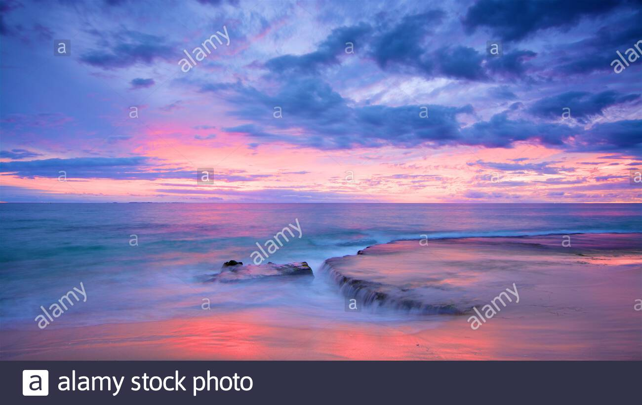 a-bright-sunset-at-north-cottesloe-beach-with-water-cascading-over-the-reef-perth-western-australia-2D78E0B.jpg