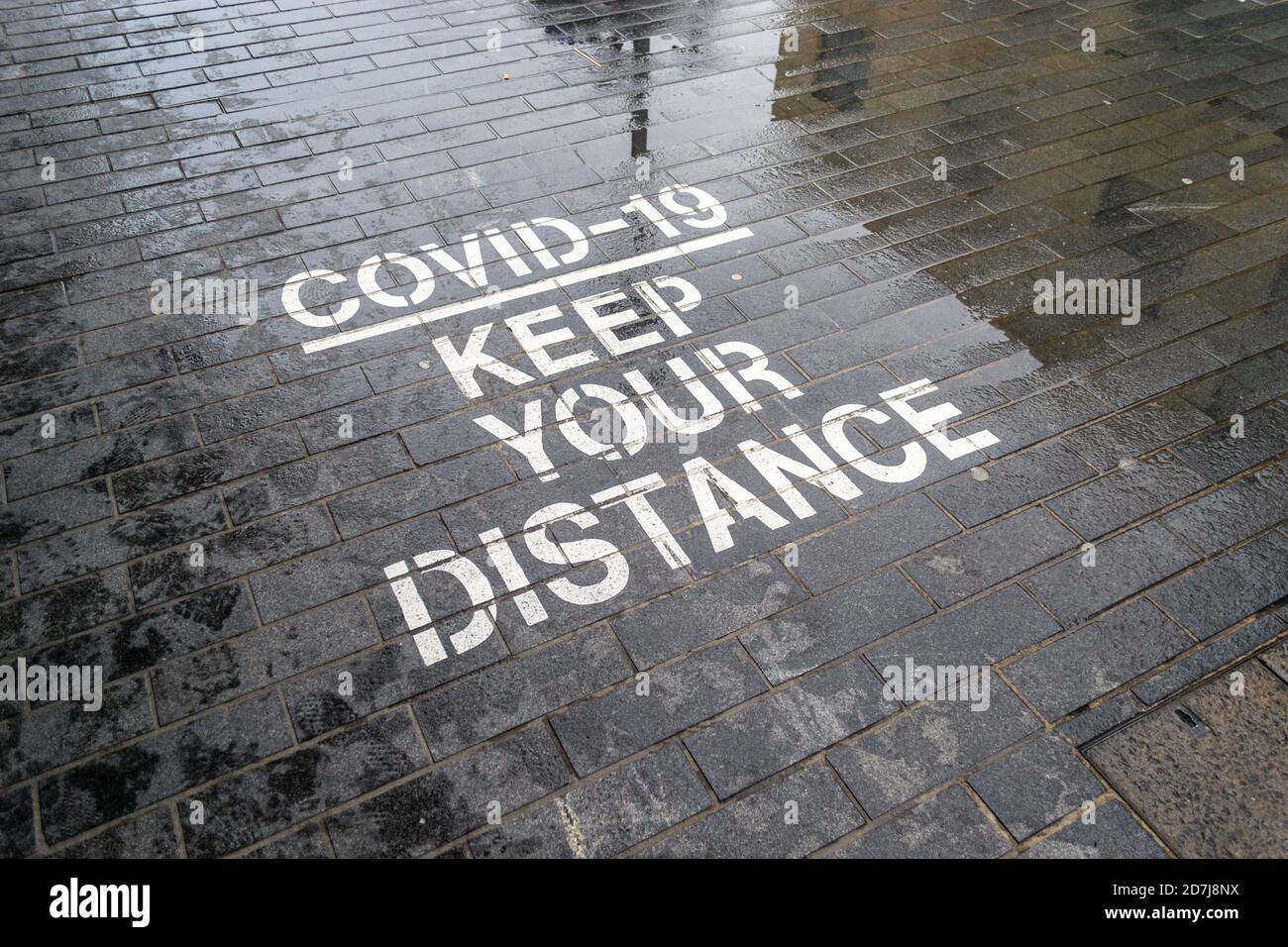 covid-19-keep-your-distance-stenciled-road-sign-social-distancing-birmingham-uk-2D7J8NX.jpg
