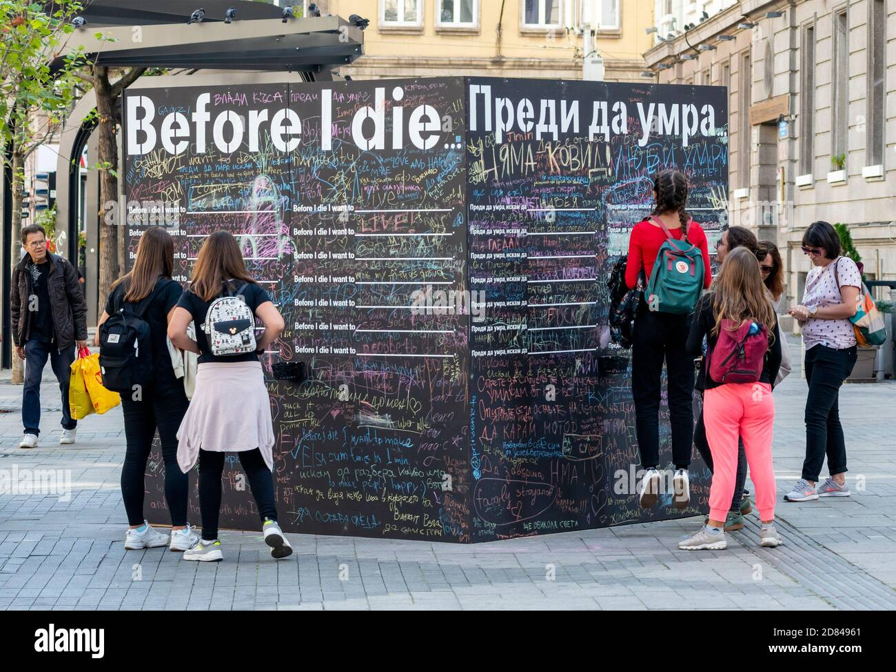 Group of teenage girls hanging out by a blackboard or chalkboard wall for the Before I Die public interactive art project in Sofia Bulgaria Stock Photo