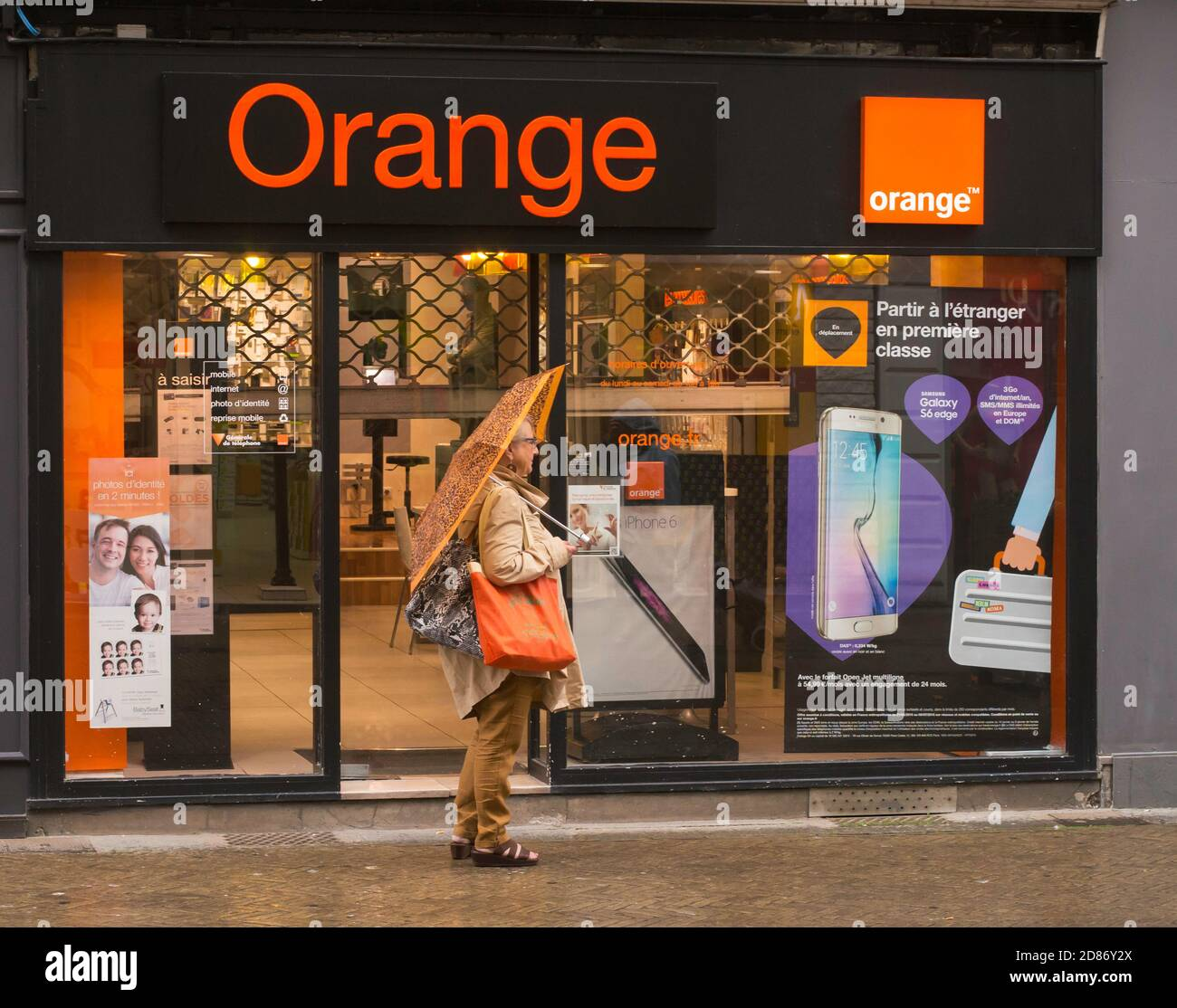 a-woman-with-an-orange-umbrella-and-bag-
