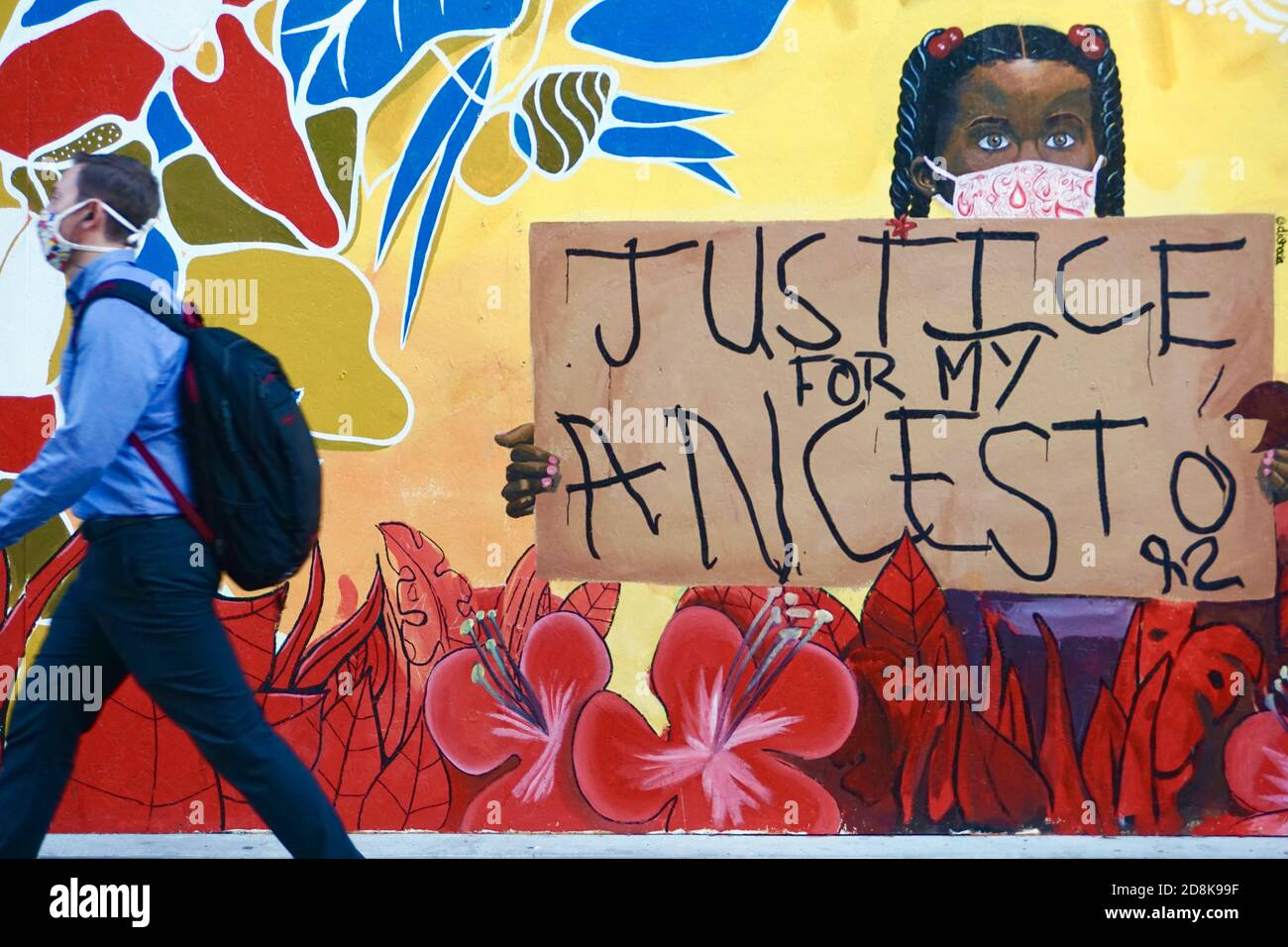 black-lives-matter-mural-in-downtown-oakland-of-an-african-american-girl-holding-a-sign-that-says-justice-for-my-ancestor-as-pedestrian-walks-by-2D8K99F.jpg