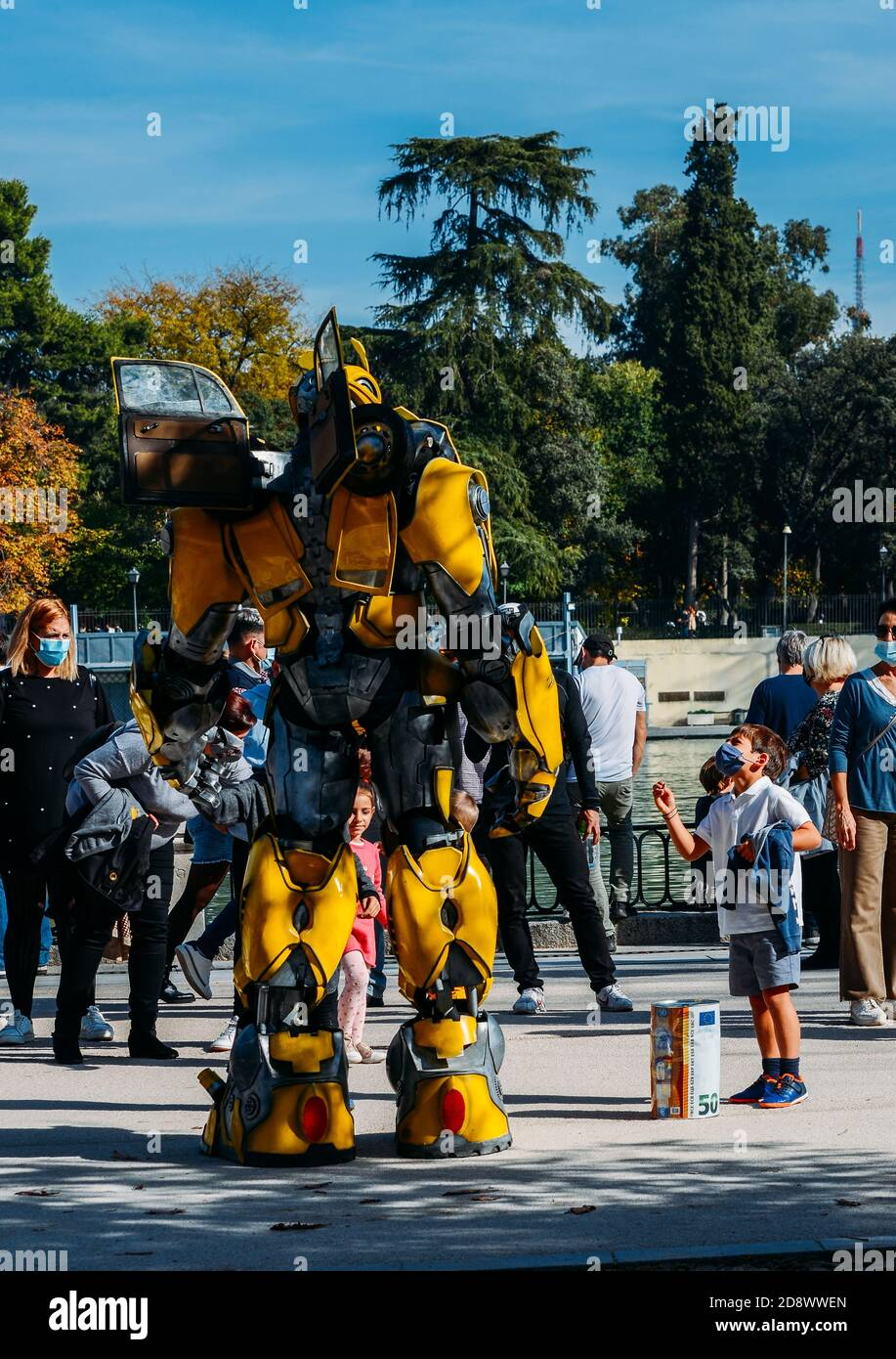 transformers-street-performer-receives-a-coin-from-a-child-at-retiro-park-in-madrid-spain-2D8WWEN.jpg