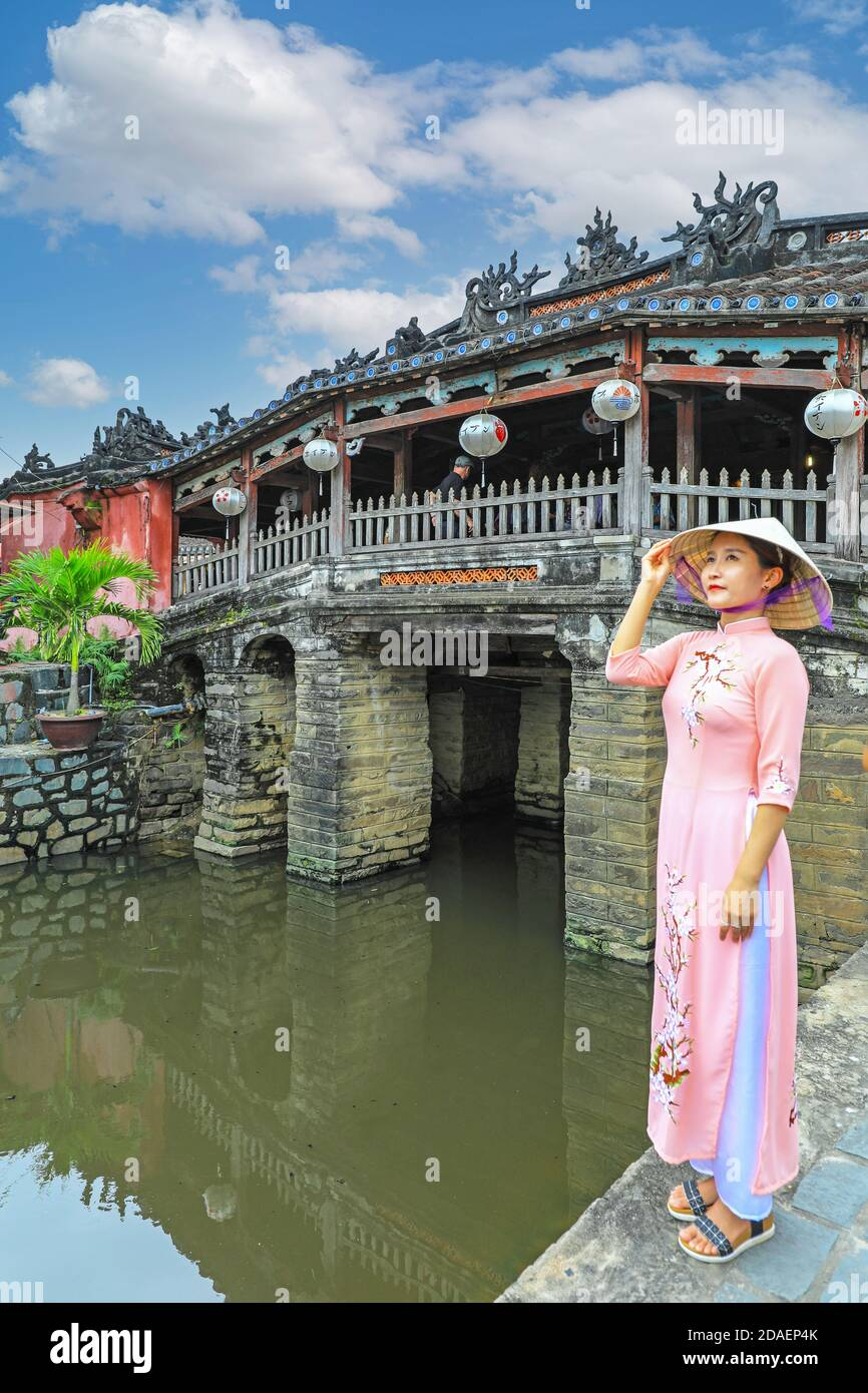 a-vietnamese-young-lady-in-traditional-dress-the-ao-dai-posing-for-a-photograph-at-the-japanese-covered-bridge-hoi-an-vietnam-asia-2DAEP4K.jpg