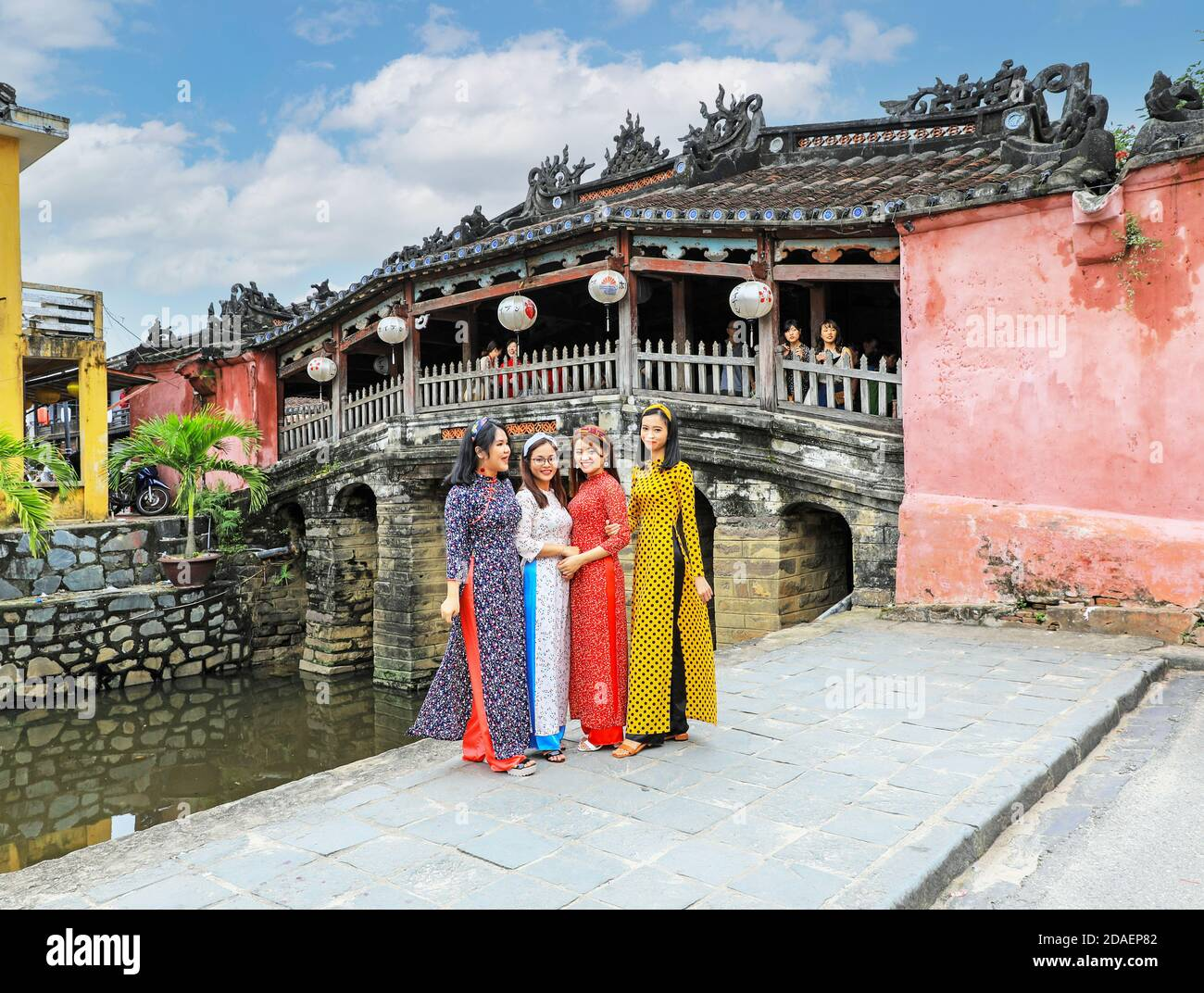 four-vietnamese-young-ladies-in-traditional-dress-the-ao-dai-posing-for-a-photograph-at-the-japanese-covered-bridge-hoi-an-vietnam-asia-2DAEP82.jpg