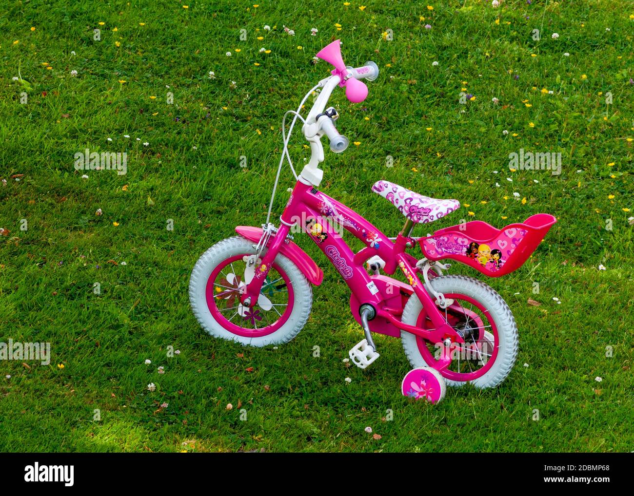 12 inches pink girl's pedal bike with training wheels in open shade on green meadow backyard Stock Photo