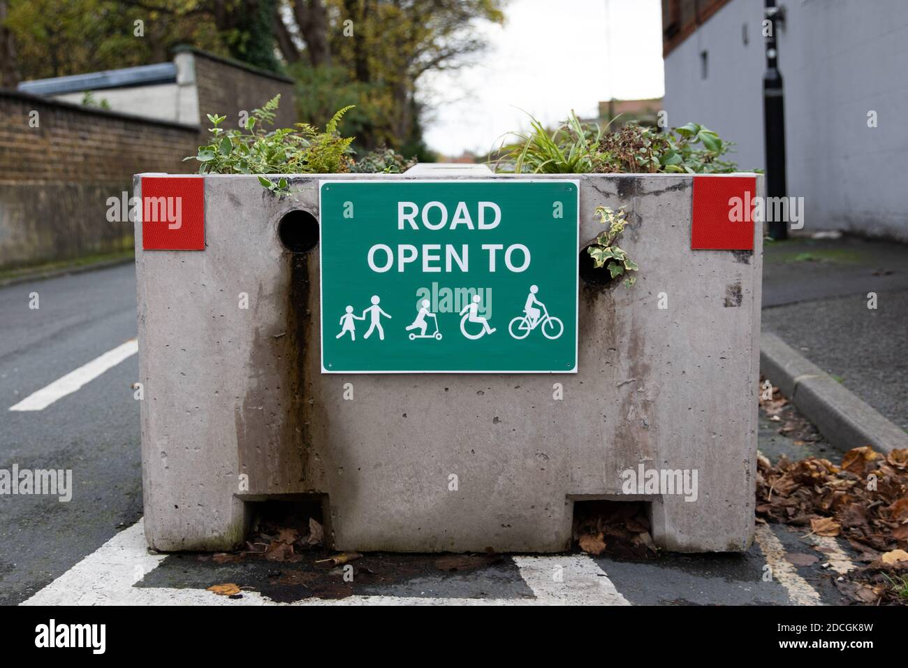 Concrete planter closing a road to motor vehicles allowing pedestrians and cyclists. Stock Photo