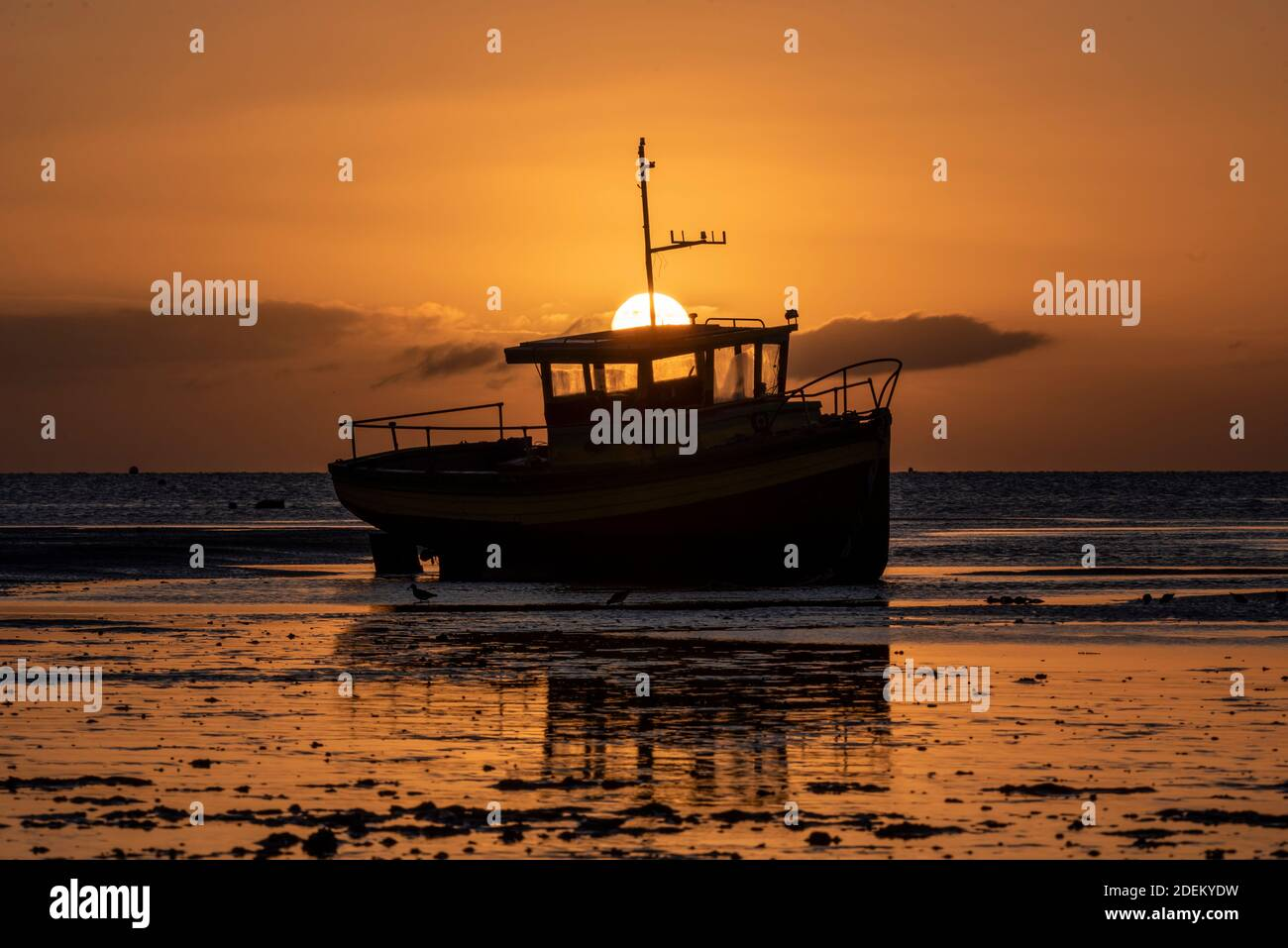 southend-on-sea-essex-uk-1st-dec-2020-the-first-day-of-december-has-dawned-bright-but-cold-with-the-sun-rising-from-behind-a-colourful-boat-moored-off-southend-on-sea-at-low-tide-vessel-sitting-on-mud-with-orange-reflection-2DEKYDW.jpg
