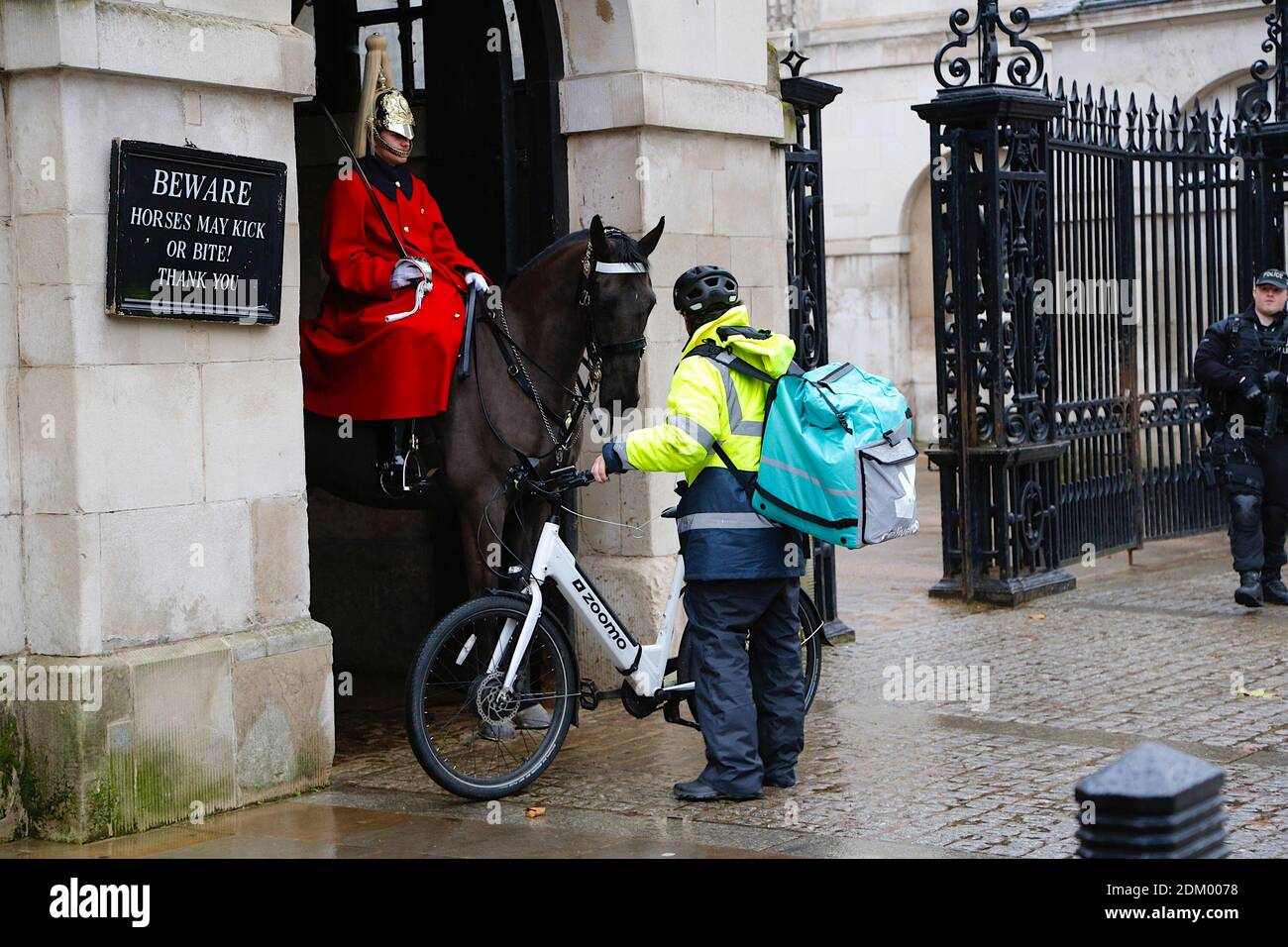Westminster, London, UK. 16 Dec, 2020. UK Weather: Chilly and drizzly rain in the West End in London. A deliveroo delivery worker asks for directions. Photo Credit: PAL Media/Alamy Live News Stock Photo
