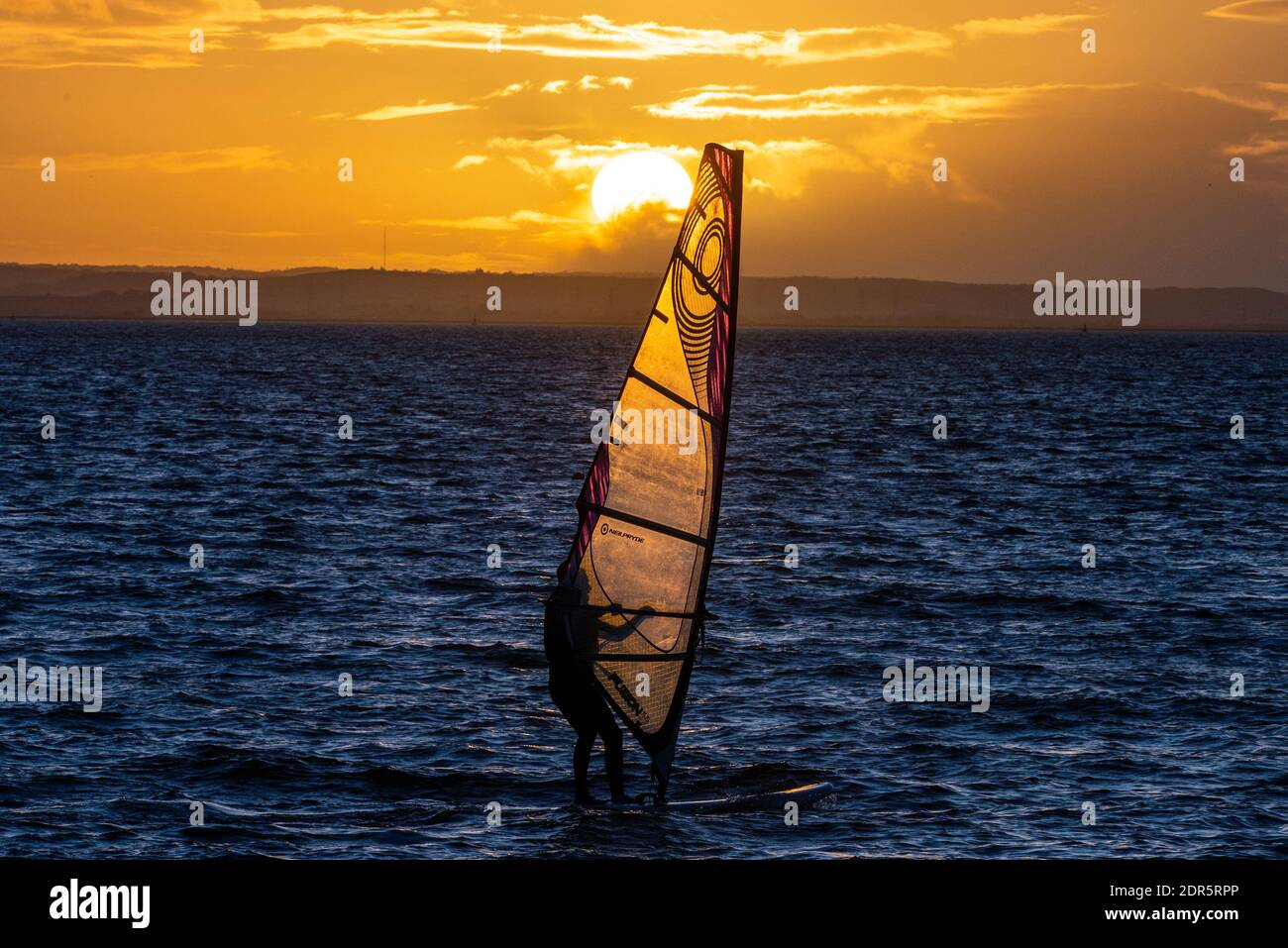 chalkwell-beach-southend-on-sea-essex-uk-20th-dec-2020-the-first-day-of-covid-alert-tier-4-in-southend-on-sea-has-ended-bright-but-cold-with-the-sun-setting-behind-a-windsurfer-out-on-the-thames-estuary-2DR5RPP.jpg