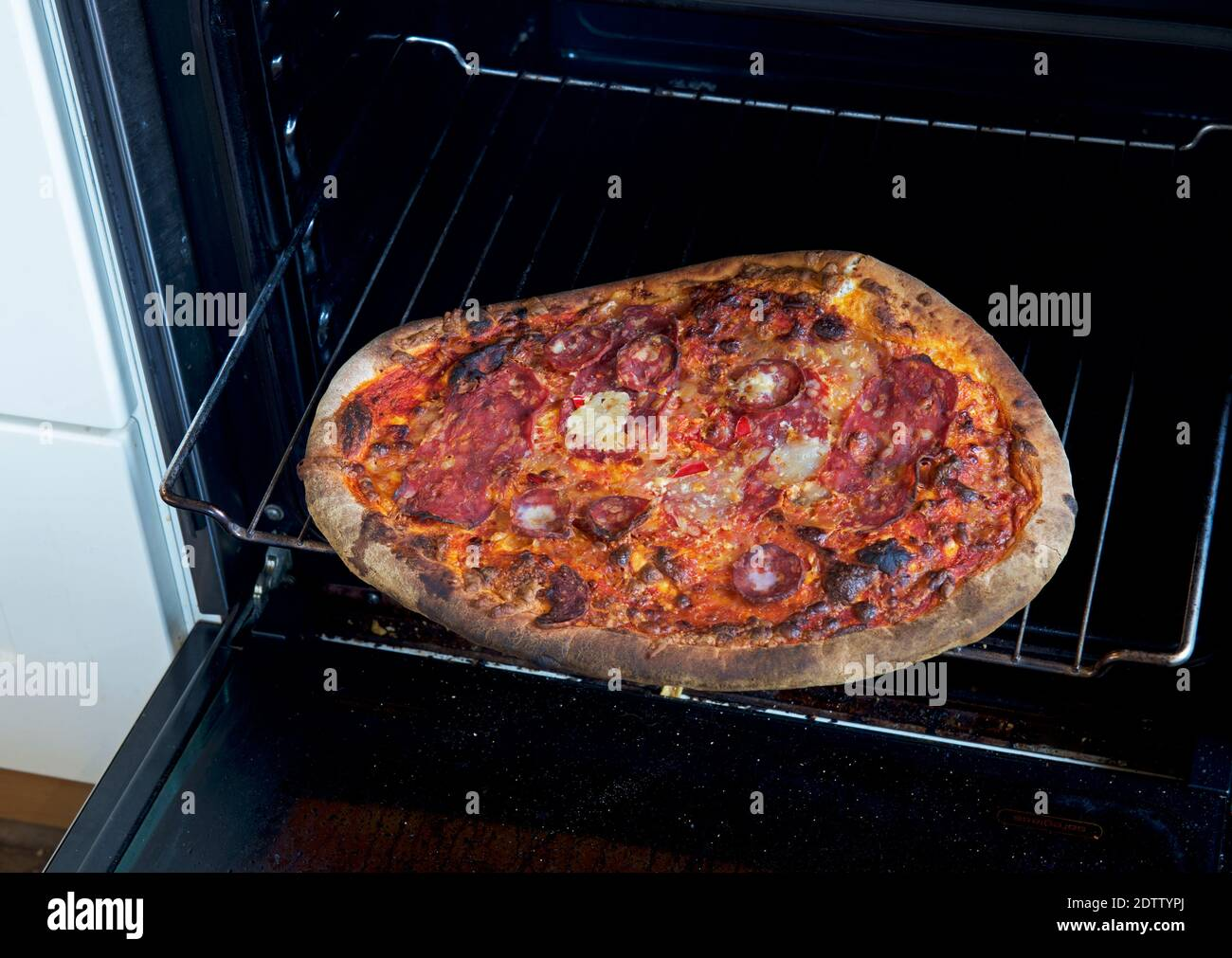 Burnt pepperoni pizza on rack in oven Stock Photo