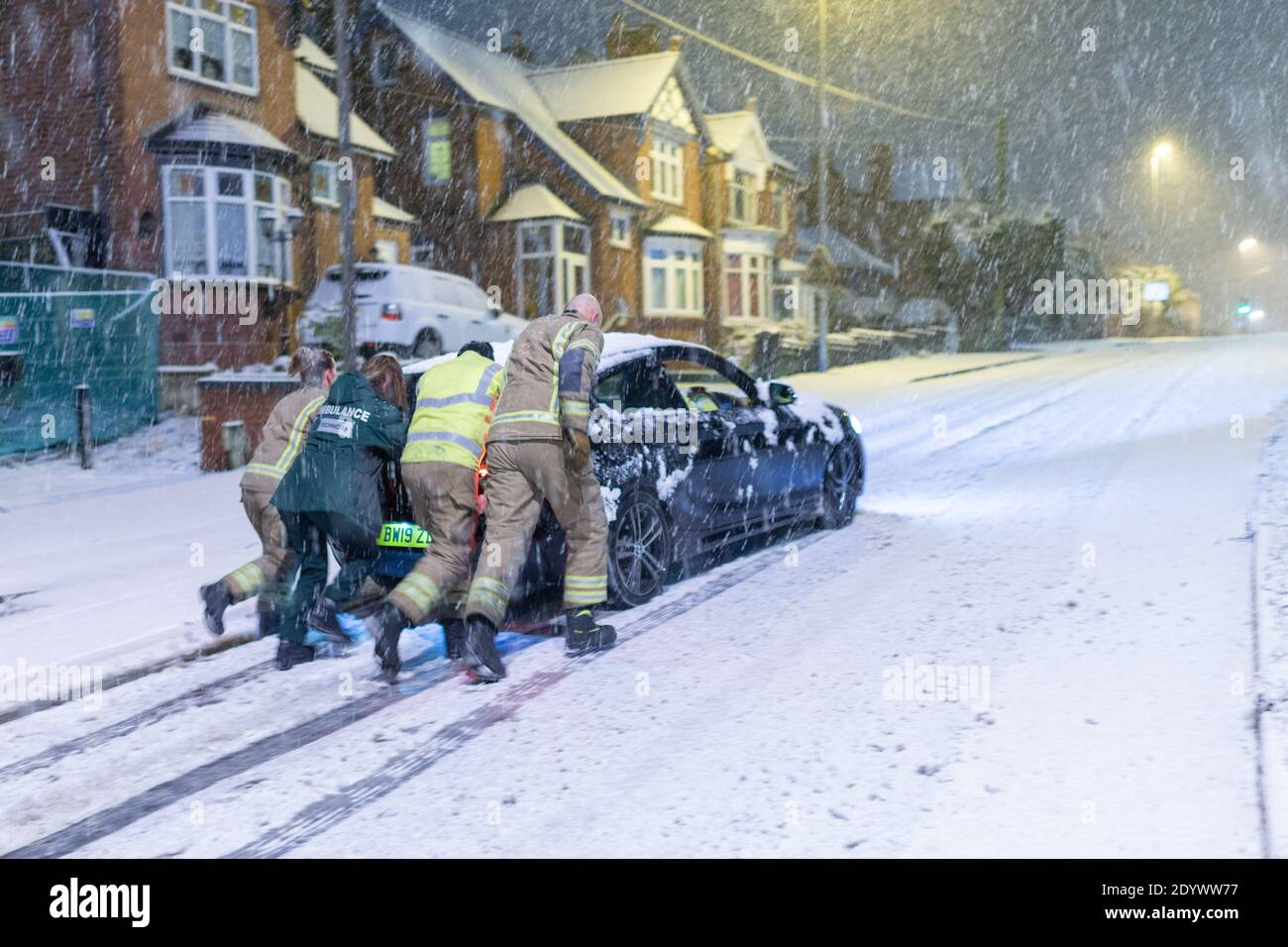 Cradley Heath, West Midlands, UK. 28th Dec, 2020. A fire crew pushes a stranded paramedic's car up a snowy hill this morning, as she tries to make it into work for her day's shift. Snow settles and causes traffic delays in Cradley Heath in the West Midlands Credit: Peter Lopeman/Alamy Live News Stock Photo