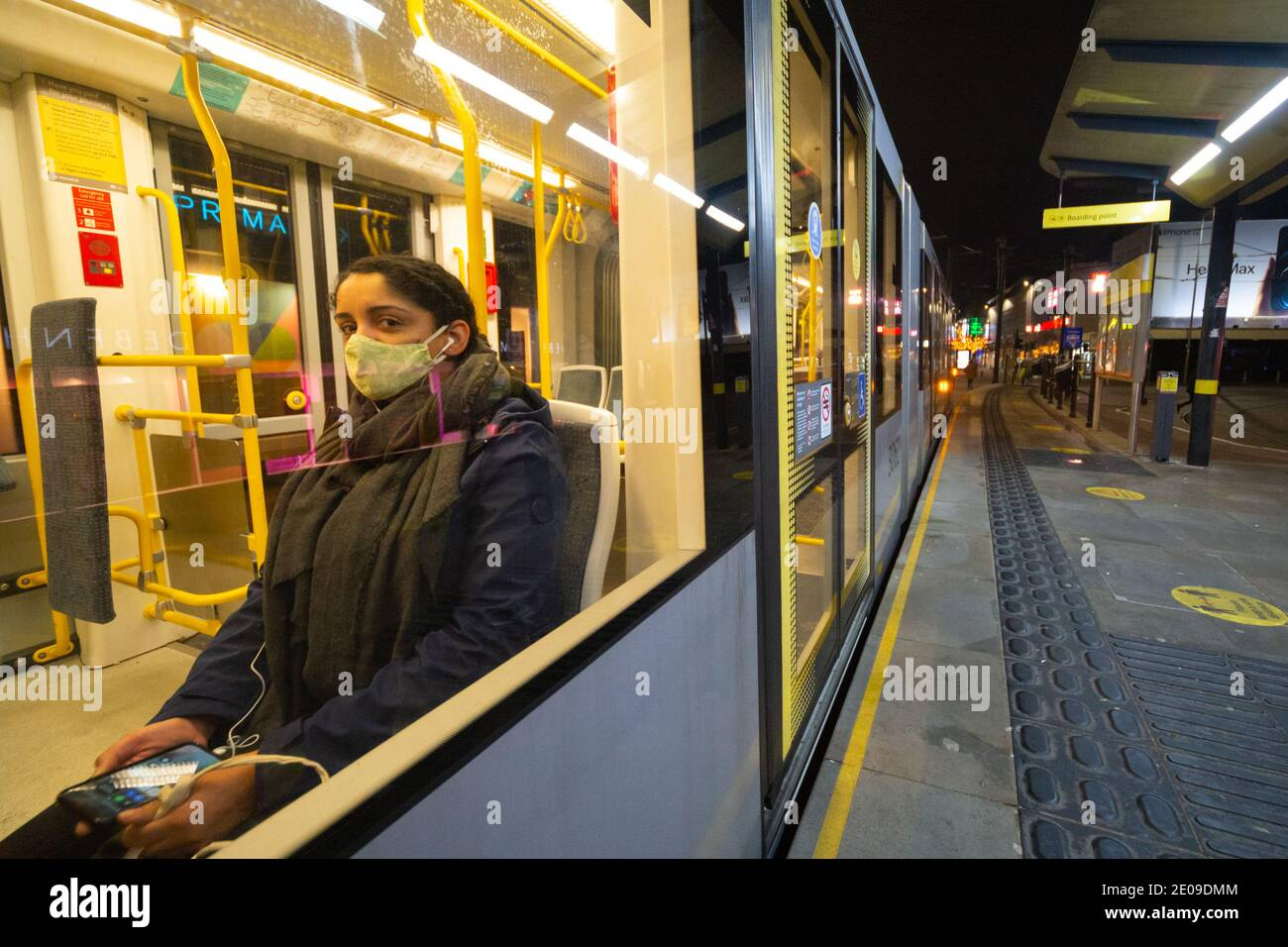 Manchester, England, UK. 30th Dec 2020. Scenes from around Manchester city centre late on the evening of the 30th. At midnight the city will be placed under Tier 4 coronavirus restrictions after a government announcement earlier today. A woman in a tram wearing a face mask makes eye contact. Credit: Callum Fraser/Alamy Live News Stock Photo