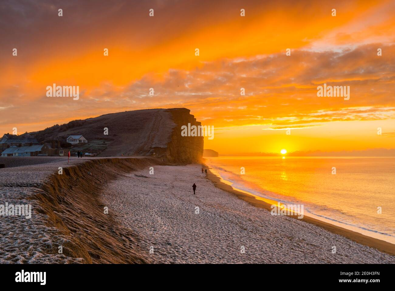 West Bay, Dorset, UK. 1st January 2021.  UK Weather.  A spectacular sunrise as the clouds glow bright orange above the frost covered beach and cliffs at West Bay in Dorset on a freezing morning on New Years Day.  Picture Credit: Graham Hunt/Alamy Live News Stock Photo