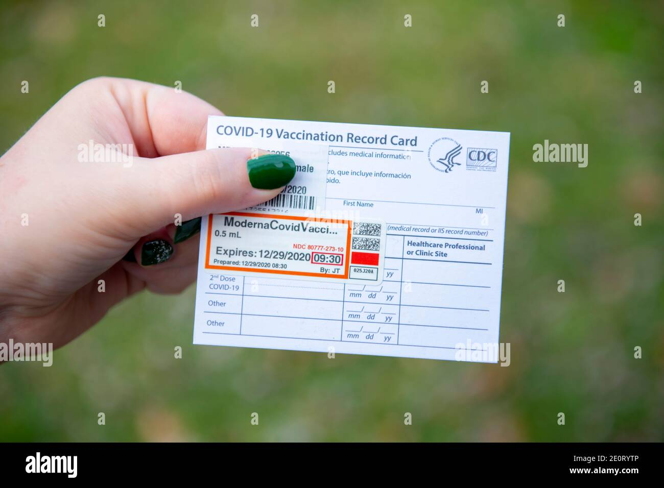 woman-holding-a-covid-19-moderna-vaccine-card-for-proof-of-the-first-dose-issued-by-the-cdc-usa-government-2E0RYTP.jpg