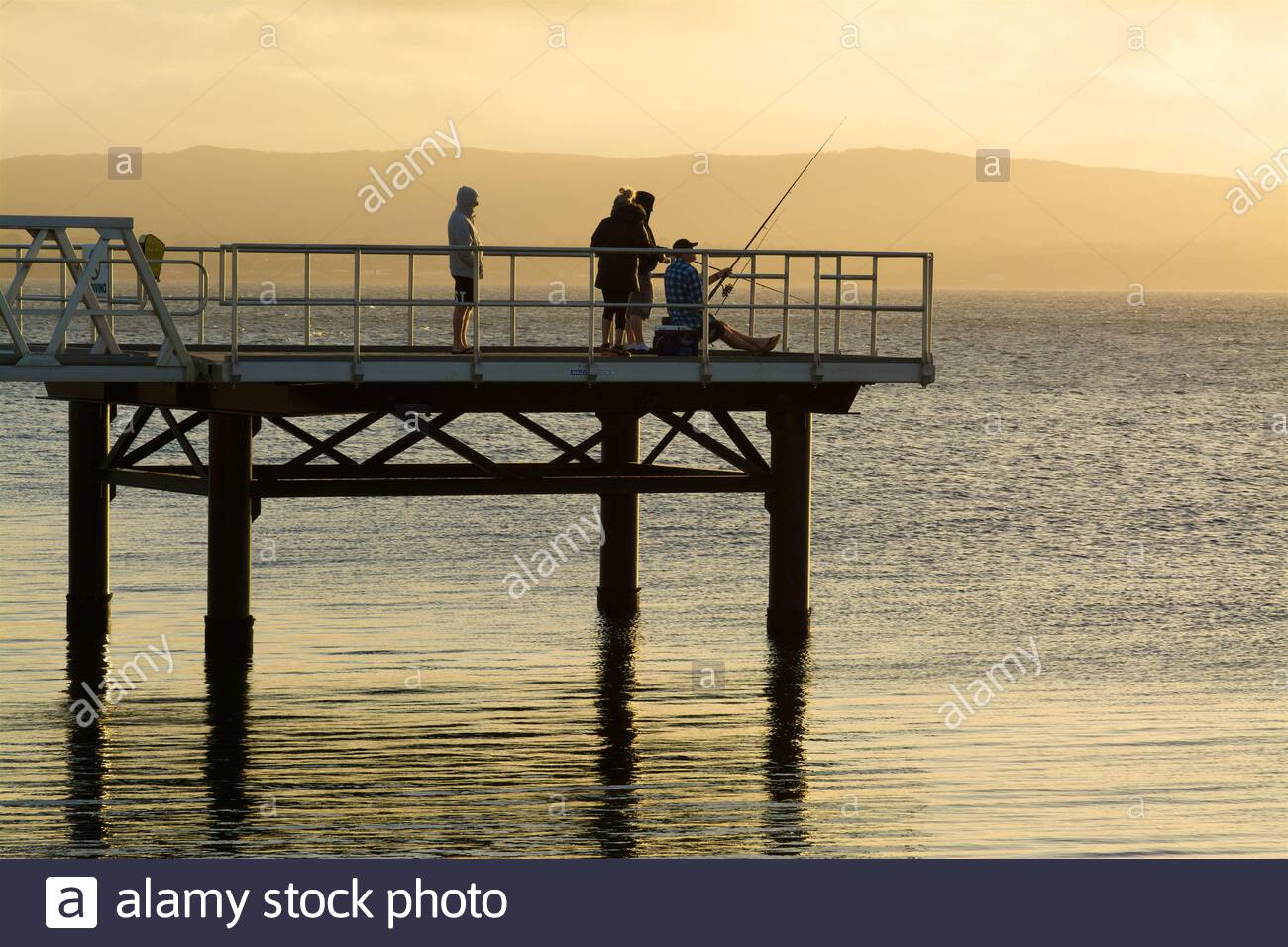 people-fishing-near-sunset-from-a-jetty-extending-from-the-waterfront-marina-in-princess-royal-harbour-albany-western-australia-2E19JXJ.jpg