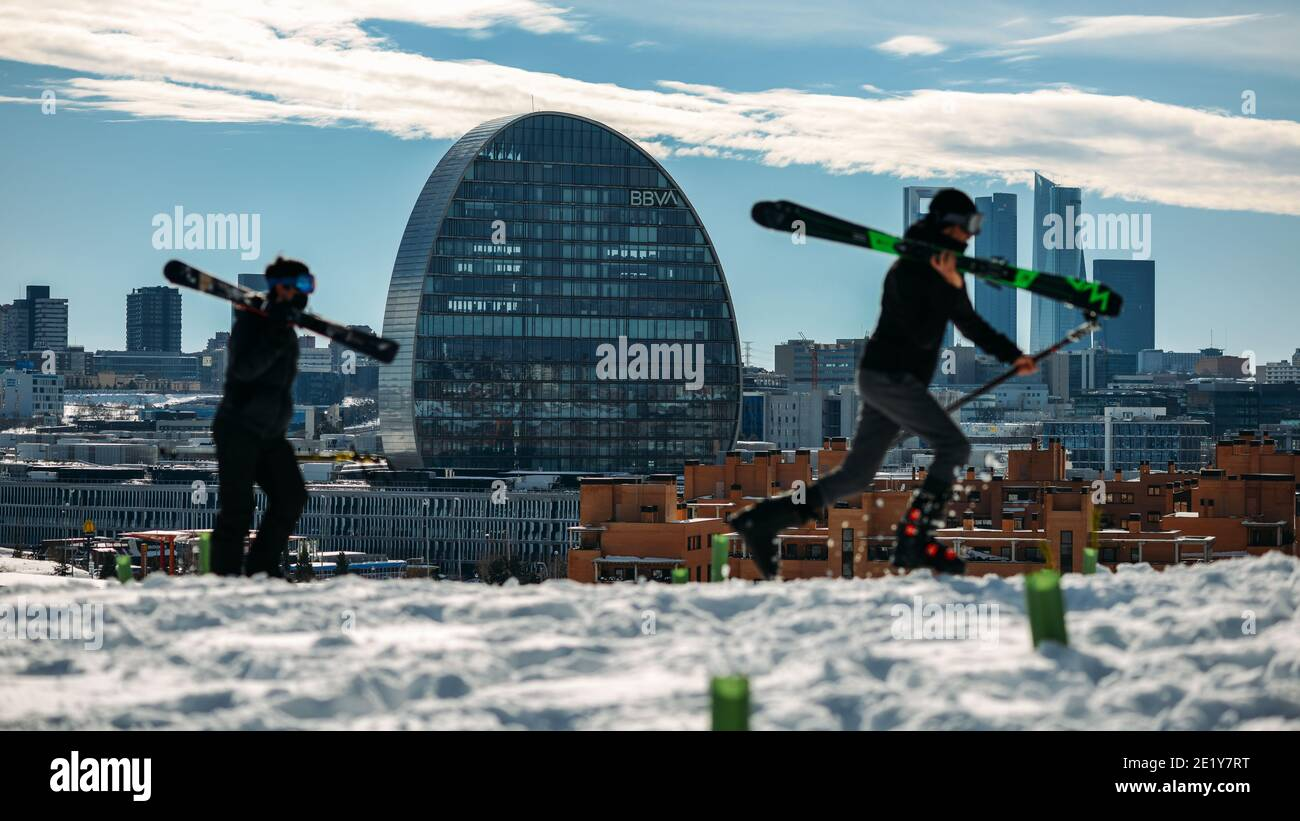 madrid-spain-january-10th-2021-a-man-and-woman-in-skis-overlooking-the-financial-district-skyscrapers-in-madrid-during-a-heavy-snowfall-2E1Y7RT.jpg