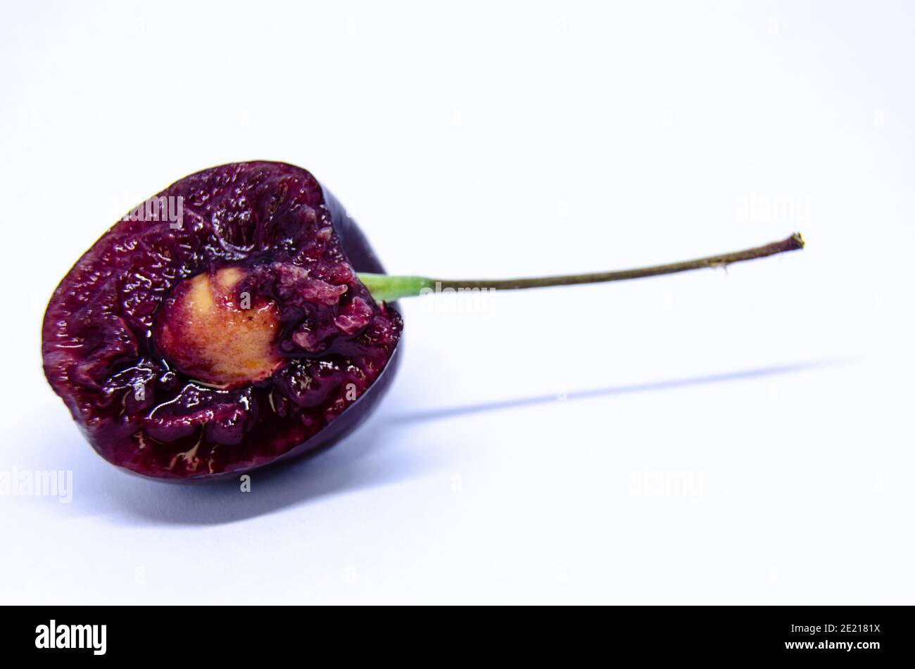 a-single-cherry-with-a-bite-taken-out-of-it-showing-the-seed-and-juicy-flesh-inside-isolated-on-a-white-background-2E2181X.jpg