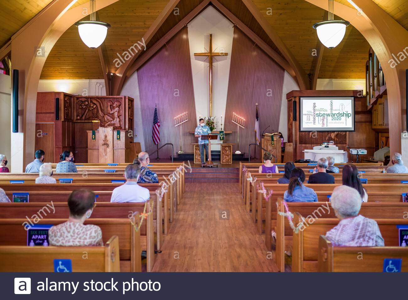 Masked pastor standing at lectern during Sunday morning worship as worshipers sitting in pews follow Hawaii state mandates during 2020 pandemic Stock Photo