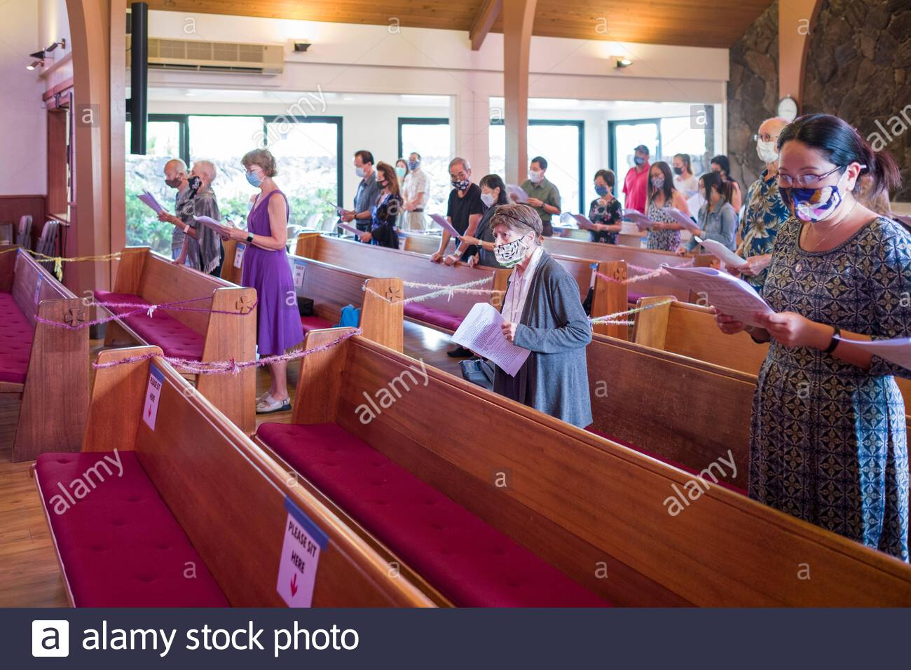 People standing during Sunday morning worship as worshipers follow Hawaii state mandates during 2020 Novel coronavirus pandemic by wearing masks Stock Photo
