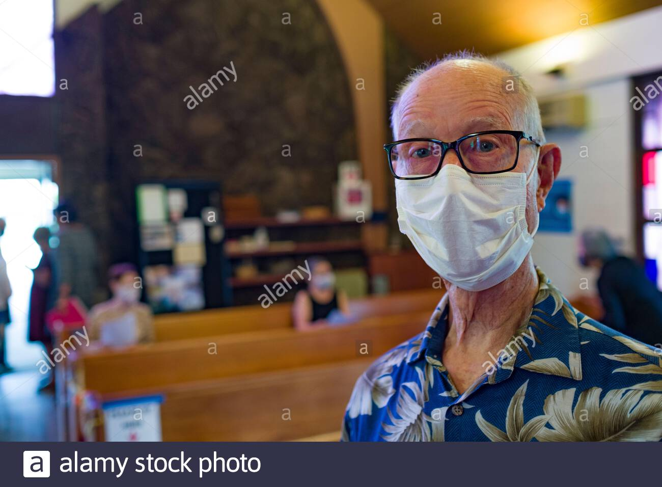 Elderly Caucasian man wearing a protective mask as required by state mandates during 2020 Novel coronavirus pandemic Stock Photo