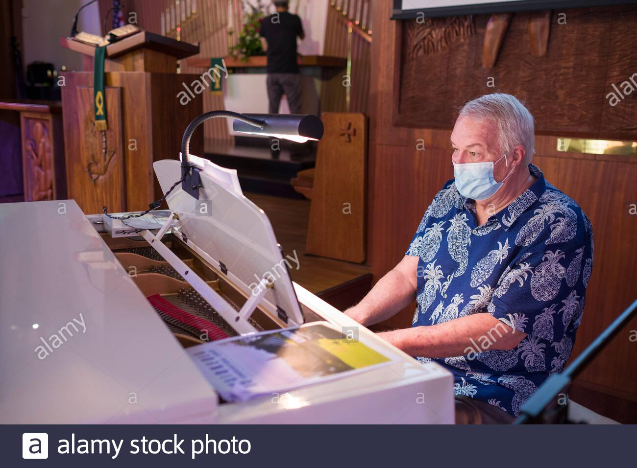 Pianist performing during Sunday morning worship wearing a mask that cover his mouth and nose as required by state mandates during 2020 pandemic Stock Photo