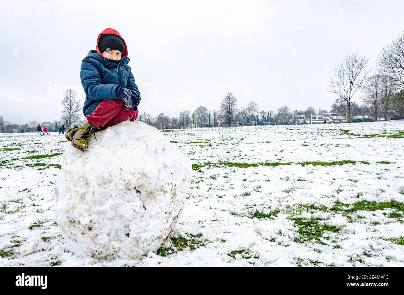 a-boy-sits-on-a-huge-boulder-made-of-snow-in-prospect-park-in-reading-berkshire-uk-2E4MXFG.jpg