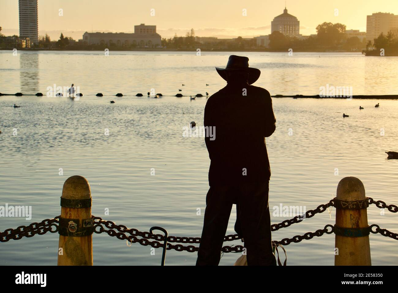 Silhouette of man standing in front of Lake Merritt at sunset in front of chain links, Oakland, California, USA Stock Photo