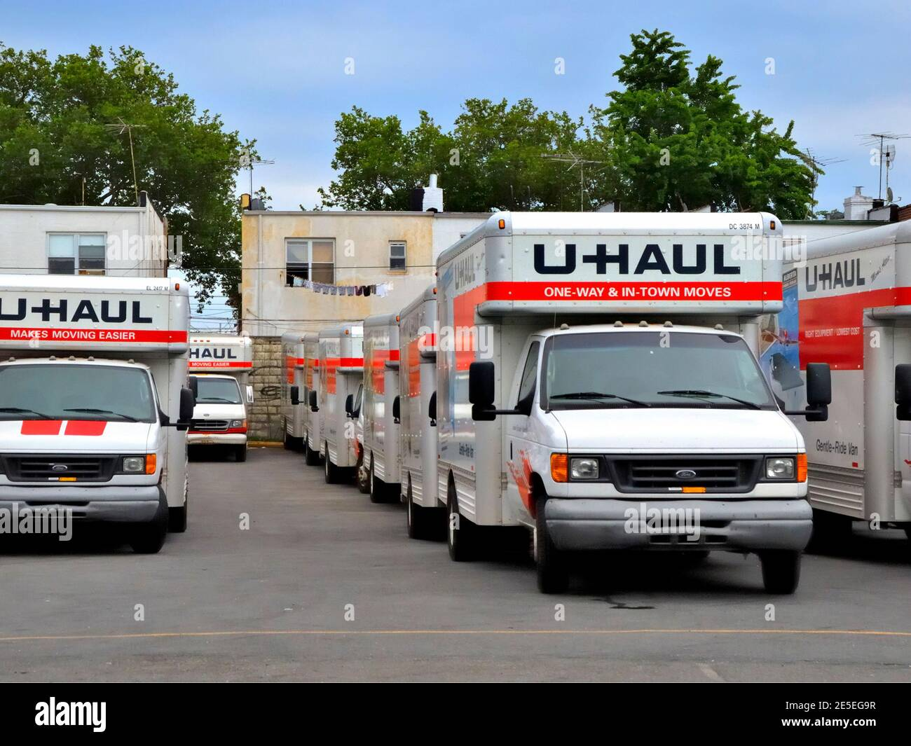 Rows of U-Haul trucks removal vans lined up in a Brooklyn New York depot parking lot moving house do-it-yourself DIY concept Stock Photo