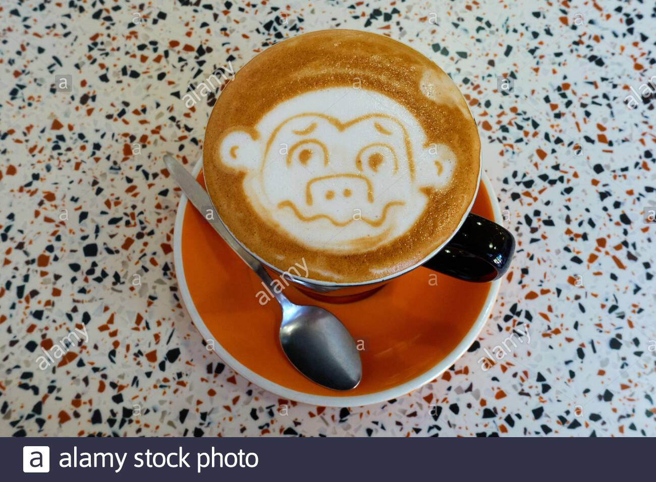 a-monkey-design-in-the-froth-on-top-of-a-flat-white-coffee-in-a-black-mug-on-an-orange-saucer-with-a-teaspoon-on-a-table-with-black-and-orange-flecks-2E6ET0C.jpg