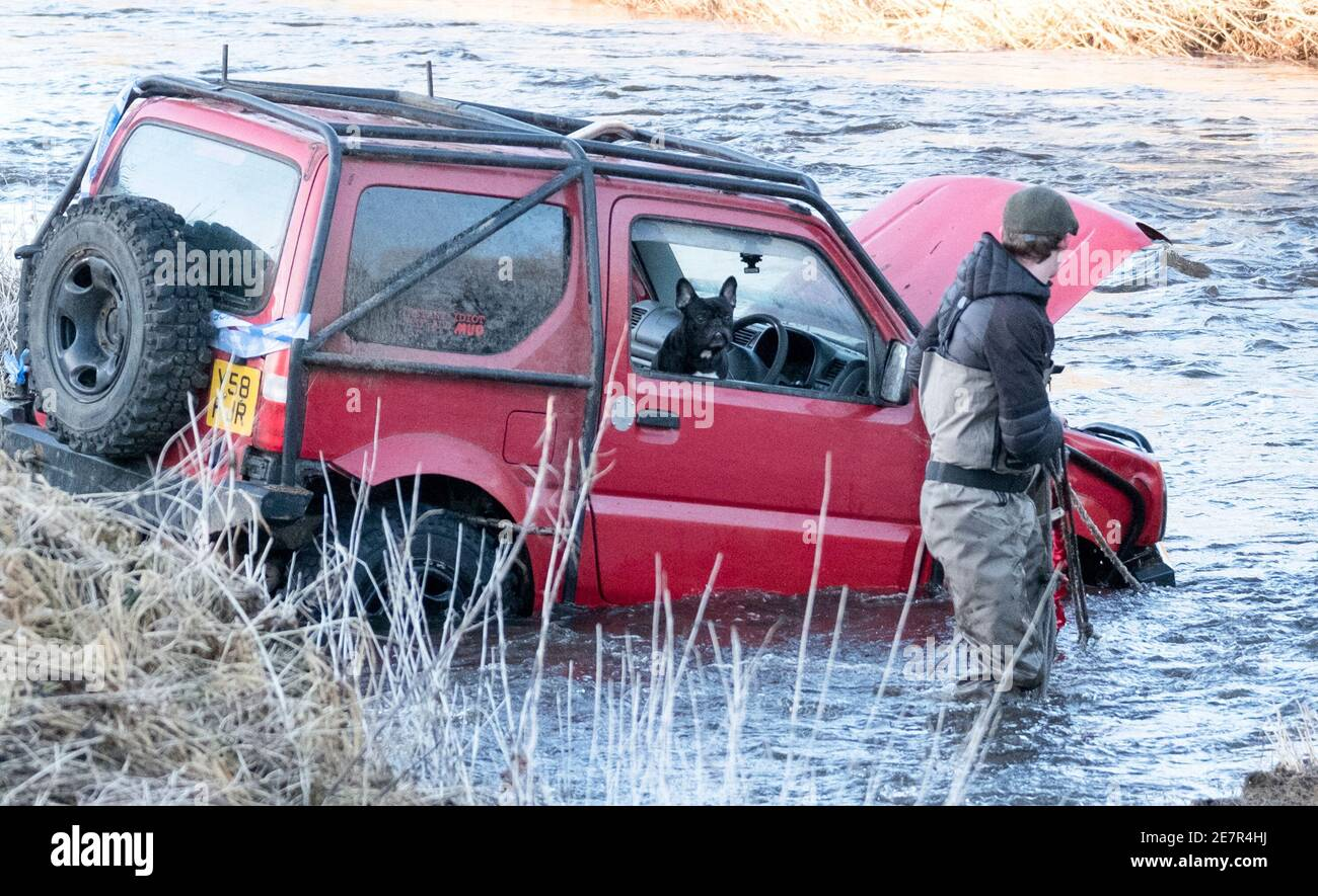 River rescue West Lothian, Scotland, UK. 3rd December, 2020. A man recovers a Suzuki Jimny vehicle with dog aboard from the River Almond, West Lothian, Scotland UK.     Credit: Ian Rutherford/Alamy Live News. Stock Photo