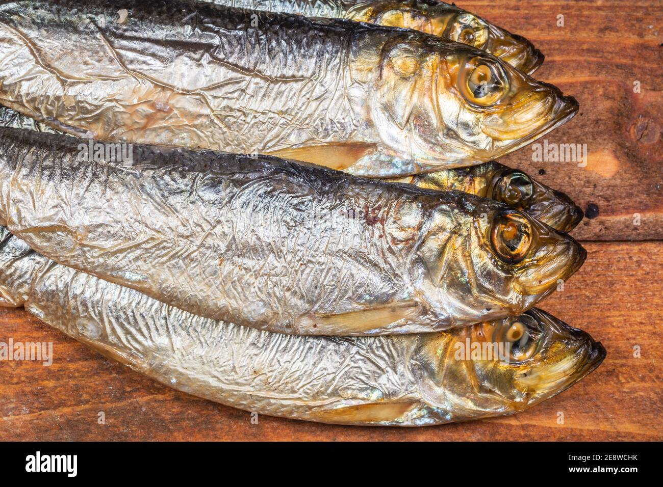 Smoked Baltic herrings (Clupea harengus membras) on an old wooden table Stock Photo