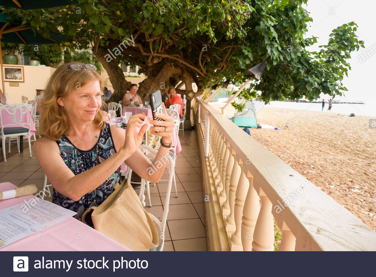 Woman using her smartphone to photograph Kaimana Beach from table in the Hau Tree Lanai restaurant, Kaimana Beach Hotel, Honolulu, Oahu, Hawaii, USA Stock Photo