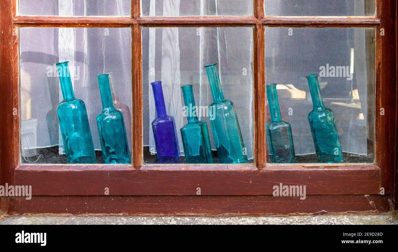 seven-blue-glass-bottles-on-display-on-a-window-sill-2E9D28D.jpg
